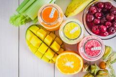 Batidos coloridos em umas garrafas da manga, laranja, banana, aipo, bagas, em uma tabela de madeira Fotos de Stock Royalty Free