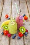 Batidos de fruta misturados frescos em umas garrafas de leite do vintage imagens de stock