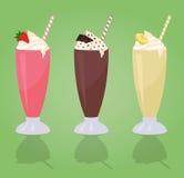 Batidos de leche clásicos con crema en el vidrio - fresa - chocolate - plátano Imagen de archivo