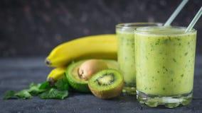 Batidos dos abacates, das bananas, do quivi e das ervas em uma tabela de madeira Alimento do vegetariano da dieta Imagens de Stock