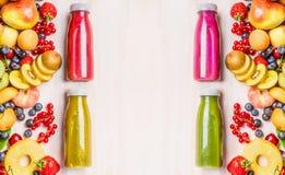 Batidos e bebidas vermelhos, cor-de-rosa, verdes e amarelos dos sucos em umas garrafas com os vários frutos e ingredientes orgâni Fotografia de Stock Royalty Free