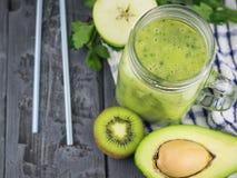 Batidos recentemente feitos do abacate com ervas e duas palhas do cocktail em uma tabela de madeira Alimento do vegetariano da di Imagem de Stock