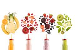 Batidos saudáveis diferentes em umas garrafas com os ingredientes frescos isolados no branco Fotografia de Stock Royalty Free