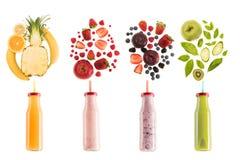 Batidos saudáveis diferentes em umas garrafas com os ingredientes frescos isolados no branco Fotos de Stock Royalty Free