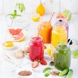 Batidos, sucos, bebidas, variedade das bebidas com frutos frescos e bagas em um fundo de madeira branco Imagem de Stock