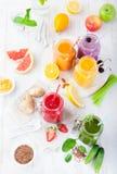 Batidos, sucos, bebidas, variedade das bebidas com frutos frescos e bagas em um fundo de madeira branco Imagens de Stock