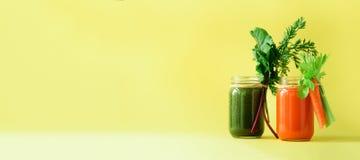 Batidos verdes e alaranjados orgânicos saudáveis no fundo amarelo bandeira Bebidas da desintoxicação no frasco de vidro dos veget Imagens de Stock