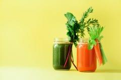 Batidos verdes e alaranjados orgânicos saudáveis no fundo amarelo A desintoxicação bebe no frasco de vidro dos vegetais - cenoura Foto de Stock Royalty Free