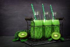 Batidos verdes em umas garrafas de leite em uma cesta do vintage contra a ardósia Fotografia de Stock Royalty Free