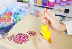 Batik process: artist paints on fabric, Batik painting Stock Image