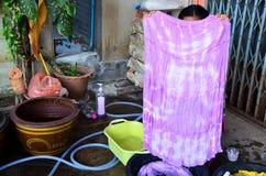 Batik tailandés del lazo de la tela de la demostración de la mujer que teñe color natural amarillo Foto de archivo