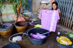 Batik tailandés del lazo de la tela de la demostración de la mujer que teñe color natural amarillo Foto de archivo libre de regalías