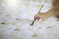 Batik Tulis dell'oro del disegno sul tessuto immagine stock