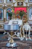 Batismo de uma criança na igreja ortodoxa ucraniana Tabela do ` s do senhor e bacia grande de água para o batismo de um bebê foto de stock royalty free
