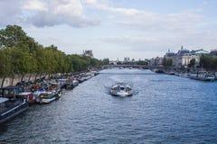 Batobus och husbåtar på Seinen i Paris Fotografering för Bildbyråer