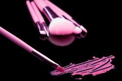 Batom com uma composição da escova no preto Imagem de Stock Royalty Free