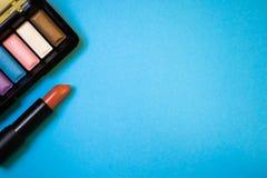 Batom e paleta colorida da sombra para os olhos no backgroun do papel azul Imagem de Stock