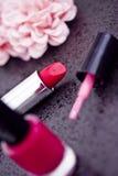 Batom vermelho, lustrador de prego & pétalas cor-de-rosa imagens de stock royalty free