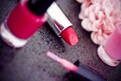 Batom vermelho, lustrador de prego & pétalas cor-de-rosa imagens de stock