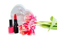 Batom vermelho, verniz para as unhas, flores da tulipa e caixa de presente de prata isolados Foto de Stock