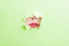 Batom vestindo da boca consideravelmente fêmea através do furo de papel rasgado Imagem de Stock Royalty Free