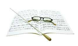Baton and glasses on music score. Isolate on white background Royalty Free Stock Photos