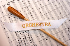 Baton & Music. A natural wood baton on a piece of music with an orchestra banner Stock Photo