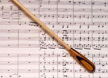 Baton & Music. A natural wood conductors baton on an orchestral score Stock Photography