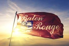 Baton Rouge city capital of Louisiana of United States flag textile cloth fabric waving on the top sunrise mist fog vector illustration