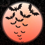 Bats against a disk of the red moon Stock Photos