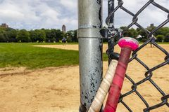 Bats by fence and batting area of base ball Diamond Central Park stock images