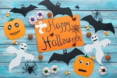 Bats, spiders, ghosts and candies. Halloween bats, spiders, ghosts and candies on blue wooden table Stock Photos