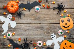 Bats, spiders, ghosts and candies. Halloween bats, spiders, ghosts and candies on grey wooden table Stock Photos
