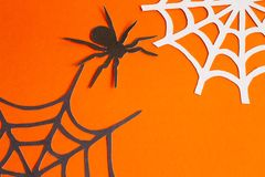 Spiders and web of paper on orange and black background stock image