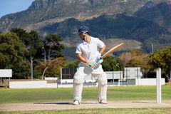 Batsman playing cricket on field against mountain. During sunny day stock photography