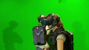 Battaglia nella realtà virtuale La gente nei caschi di VR gioca il gioco nella realtà virtuale su un fondo verde stock footage