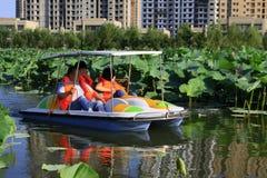 Battello da diporto che guida lentamente nell'acqua, in un parco Immagini Stock