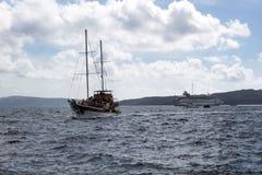 Battello da diporto con gli alberi al pilastro nel vecchio porto di Fira, Grecia, Santorini I turisti sono fotografie stock libere da diritti