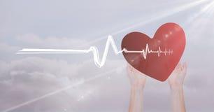 Battement de coeur au-dessus des mains tenant le coeur Photographie stock
