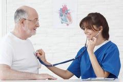 Battement de coeur de examen de docteur d'homme supérieur Photographie stock libre de droits