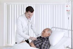 Battements de coeur de examen de docteur sur le patient hospitalisé Image stock
