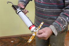 Batten and silicone glue. Plumber caulking silicone from cartridge to aluminum tile trim profile royalty free stock photo