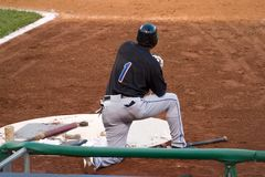 Batter on deck. A batter kneeling down near the on-deck circle of a ballpark Stock Photos