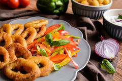 Batter fried squid rings with potato croquettes and pepper salad Stock Images