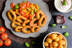 Batter fried squid rings with potato croquettes and pepper salad Royalty Free Stock Photography