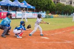 Batter hit the ball in a baseball game. ZHONGSHAN PANDA CUP, ZHONGSHAN, GUANGDONG - July 23:batter of team BeiJing TianTan DongLi Primary School hit the ball Royalty Free Stock Images