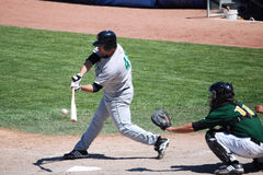 Batter hitting a ball. This is a minor league basball game of the Clinton Lumberjacks Vs. South Bend Silverhawks.  Game took place in South BEnd Indiana on 5-31 Stock Image
