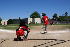 Batter hitting ball with catcher behind him. Stock Photo
