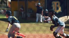 Batter hitting ball and running to first base during a baseball game. stock video footage