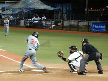 Batter swings at incoming pitch Royalty Free Stock Image